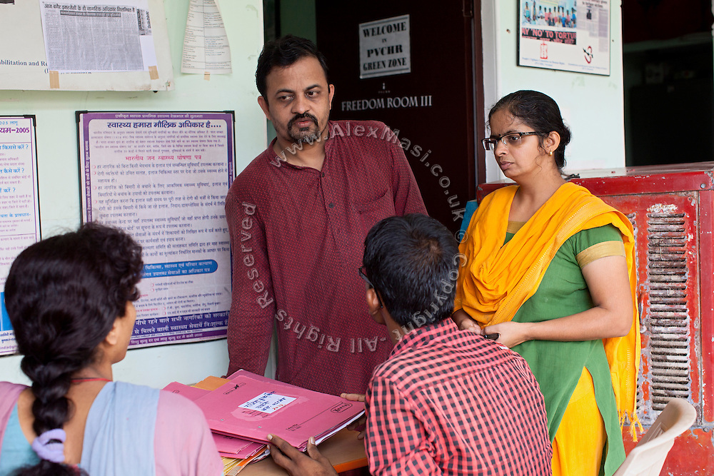 Dr Lenin Raghuvanshi, (left) and her wife (right) are listening to some of their collaborators at the PVCHR headquarters in Varanasi, Uttar Pradesh, India. Lenin's grandfather was a freedom fighter in India's fight against the British. His father was a communist, so he names all of his children after famous communists: Mao, Che Guevara, Stalin, Lenin and Raul. Lenin used to be a doctor in Ayurveda and modern medicine but quit because of the inherent corruption he witnessed. He founded PVCHR in 1996. The charity organises workshops, supports victims during trial and with the police, and promotes education and gender equality.