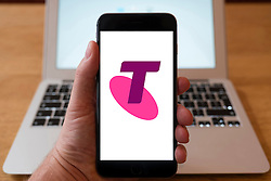 Using iPhone smartphone to display logo of Telstra, Australia's largest telecommunications and media company