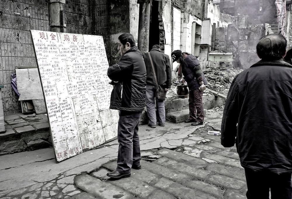 Chongqing - 11 gennaio 2011: Un uomo legge un cartellone con annunci di affitto/vendita di case nel distretto di Yuzhong. Le famiglie coinvolte nel progetto di sviluppo urbano, ricevono un contributo finanziario dal governo, ma sono lasciate sole nella scelta della loro nuova abitazione. Molto spesso sono costrette a spostarsi verso zone residenziali della città, lontane da dove abitavano. Chongqing, January 11, 2011: A man reads ads for house renting/sale near a demolished quarter near Zhonghshan Lu in Yuzhong district. The residents are given economic aid but they have to look for a new house themselves and some have to move far away from the city center.