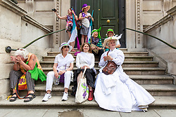 © Licensed to London News Pictures. 10/06/2018. London, UK. Participants in PROCESSIONS take a break on the steps of a private members' club on Pall Mall as thousands of people march through central London wearing green, white and violet, the colours of the Suffragette movement,  to celebrate 100 years votes for women. Photo credit: Rob Pinney/LNP