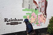 A local man walks past an artwork mural showing the small Essex town of Rainham, on 8th October 2019, in Rainham, Essex, England. Voters in this Havering borough voted 69% in favour of Brexit during the 2016 referendum.