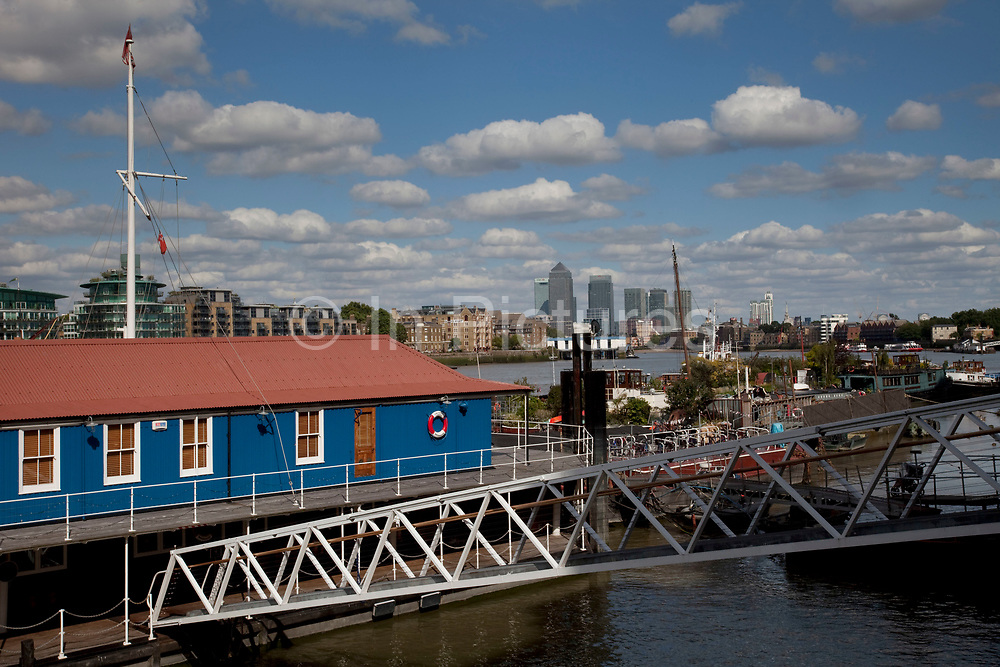 Butlers Wharf Pier, South East London. This floating building falls and rises with the River Thames tide. In the distance we see Canary Wharf, and residential buildings in Wapping.