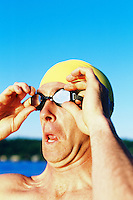 Portrait of male swimmer outside putting on goggles