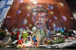 © Licensed to London News Pictures. 10/01/2017. London, UK. Tributes left beneath a mural of David Bowie in Brixton, south London, to commemorate the first anniversary of the star's death. Photo credit: Rob Pinney/LNP