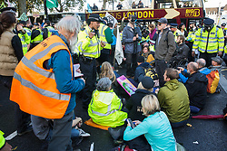 London, UK. 13 October, 2019. Police officers issue notices under Section 14 of the Public Order Act 1986 to climate activists, including disabled activists, from Extinction Rebellion protesting outside New Scotland Yard against tactics employed by police officers which impinge on the right to protest of disabled activists, including the confiscation of wheelchairs, wheelchair ramps, accessible toilets and tents.