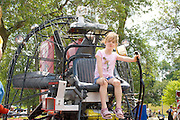 Confident young girl age 6 in drivers seat of fire dept water rescue airboat. Aquatennial Beach Bash Minneapolis Minnesota USA