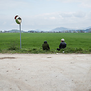 An elderly Kurdish couple sitting by a green field near Idomeni, Greece. In front of them is the border. <br /> <br /> Thousands of refugees are stranded in Idomeni unable to cross the border. The facilities are stretched to the limit and the conditions are appalling.