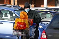 © Licensed to London News Pictures. 14/12/2020. London, UK. An elderly man wearing a fcae covering with shopping bags outside Sainsbury's in north London. With coronavirus restrictions  and a possible No-Deal Brexit outcome from the EU-UK trade negotiations, members of public are stocking up supplies of food items. Health officials are concerned about a sharp rise in coronavirus infection rates in London which means the capital may go into tier three tougher lockdown restrictions. Photo credit: Dinendra Haria/LNP