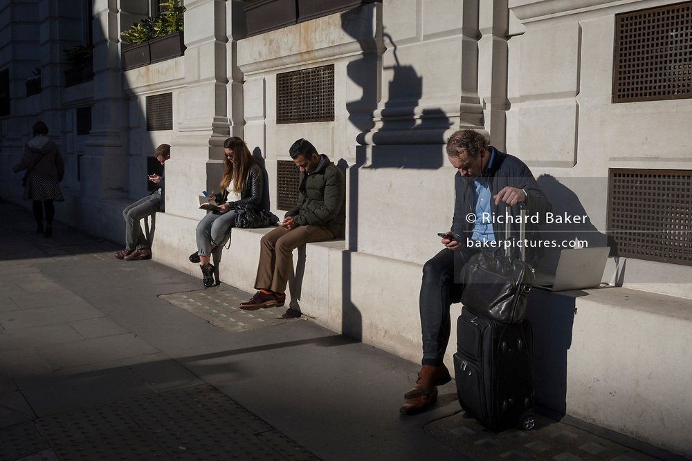City people check for messages and use social media in the street, sitting in autumn sunshine, on 27th October 2017, in the City of London, England.