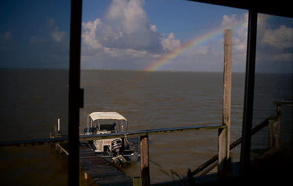 Stock photo of a boat docked to a pier with a rainbow crossing the sky