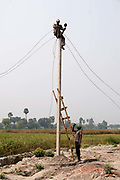 Bihar India March 2011. Installing electricity for the first time.