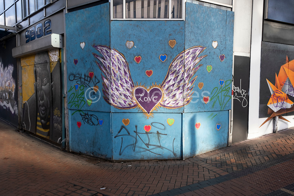 Wings of love graffiti covers some boarded up closed down shops in the City Centre on 26th November 2020 in Birmingham, United Kingdom. The national lockdown and following tier 3 status is a huge blow to the economy and for individual businesses in Britain's second city, who were already struggling after eight months of Covid-19 restrictions. In tier 3 people can only meet other households in outdoor public spaces like parks, where the rule of six applies.