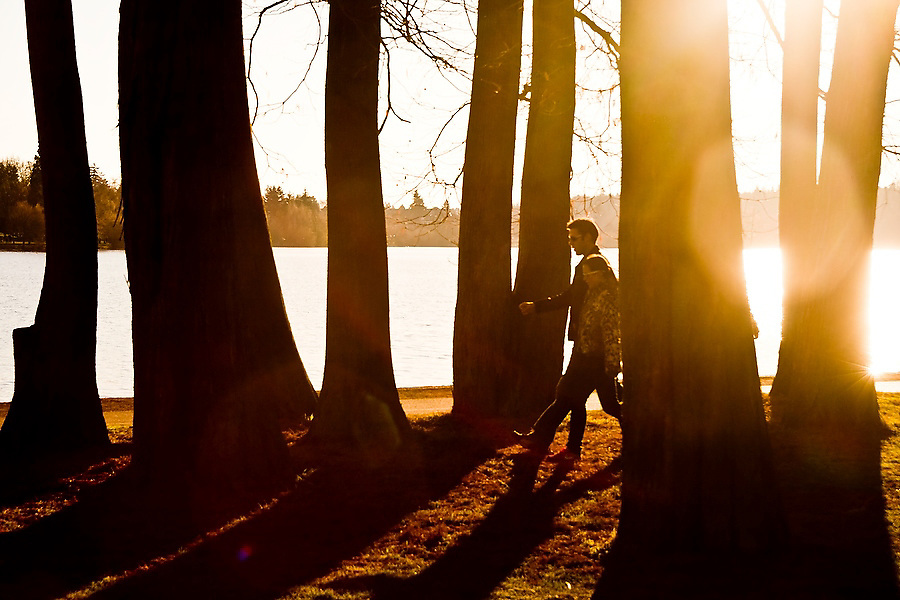 A young couple walks through a stand of trees at sunset along the shore of Green Lake, a popular pedestrian park in Seattle, Washington.