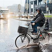 Nederland Rotterdam 26 augustus 2011 20110826 Zware regenval in kort tijdsbestek zorgt voor wateroverlast op Rotterdam Weena. De riolering / afvoer systeem voor het water kan de grote hoeveleelheid water niet aan, met als gevolg een grote plas water op het wegdek. Fietser in regenpak doorkruist de plas water met opgetrokken benen om natte voeten te voorkomen.  Foto: David Rozing