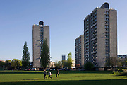 People walk through the green space between high-rise flats in Kennington Park, Lambeth, South London. The three blocks of flats (apartments) are multi-storey and house poorer south London families. Kennington Park is in Kennington in London, England, and lies between Kennington Park Road and St Agnes Place. It was opened in 1854. Previously the site had been Kennington Common. This is where the Chartists gathered for their biggest 'monster rally' on 10 April 1848. Soon after this demonstration the common was enclosed and, sponsored by the royals, made into a public park. Kennington Common was a site of public executions until 1800 as well as being the South London's area of Public speaking. Some of the most illustrious orators to speak here were Methodist founders George Whitefield and John Wesley who is reputed to have attracted a crowd of 30,000.