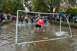 © Licensed to London News Pictures; 30/08/2021; Bourton-on-the-Water, UK. A goal is scored from a penalty kick in the century-old Gloucestershire tradition of five-a-side football played in the river Windrush every August Bank Holiday, drawing hundreds of spectators. Goalposts are set up in the river and two teams from Bourton Rovers 1st XI and 2nd XI battle it out for the honours attempting to score as many goals as possible. The match ended in a draw 1-1. Local legend has it that the event began when drunken football fans spilled out of the nearby Kingsbridge Inn to play an impromptu match. Photo credit: Simon Chapman/LNP.