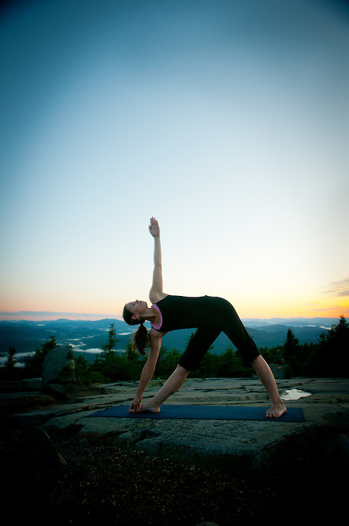 A woman does Yoga on a mountain top at sunrise.