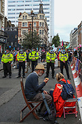 Two XR activists are sat in St Martins Lane as police observe an Extinction Rebellion climate protest near Covent Garden in central London on Monday, Aug 23, 2021. This is a two week planned of action against new fossil fuel investments. XR protestors are aiming to occupy parts of central London for two weeks from Monday, aiming to force the Government to halt all new investment in fossil fuels. (VX Photo/ Vudi Xhymshiti)