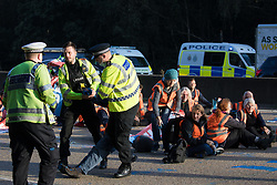 Ockham, UK. 21st September, 2021. Surrey Police officers haul an Insulate Britain climate activist from the clockwise carriageway of the M25 between Junctions 9 and 10. Activists briefly halted traffic on both carriageways of the motorway as part of a campaign intended to push the UK government to make significant legislative change to start lowering emissions.