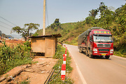 14 MARCH 2013 - ALONG HIGHWAY 13, LAOS:  A Chinese truck drives down Highway 13 in the Boten Special Economic Zone in northern Laos, a few miles short of the Chinese border. The paving of Highway 13 from Vientiane to near the Chinese border has changed the way of life in rural Laos. Villagers near Luang Prabang used to have to take unreliable boats that took three hours round trip to get from the homes to the tourist center of Luang Prabang, now they take a 40 minute round trip bus ride. North of Luang Prabang, paving the highway has been an opportunity for China to use Laos as a transshipping point. Chinese merchandise now goes through Laos to Thailand where it's put on Thai trains and taken to the deep water port east of Bangkok. The Chinese have also expanded their economic empire into Laos. Chinese hotels and businesses are common in northern Laos and in some cities, like Oudomxay, are now up to 40% percent. As the roads are paved, more people move away from their traditional homes in the mountains of Laos and crowd the side of the road living off tourists' and truck drivers.    PHOTO BY JACK KURTZ