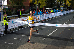 © Licensed to London News Pictures . 15/10/2017 . Manchester , UK . Men's winner LUKE TRAYNOR breaks the tape at the finish line in the Greater Manchester Half Marathon in Old Trafford . Photo credit : Joel Goodman/LNP