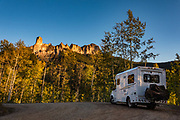 Sunset shines on Chimney Rock (11,781 ft) and Courthouse Mountain (12,152 ft), in the San Juan Mountains, near Ridgway, Colorado, USA. In our RV, we drove up to Owl Creek Pass at 10,114 feet on the steep Owl Creek-Cimarron Road, an old cattle-drive trail winding through Uncompahgre National Forest.