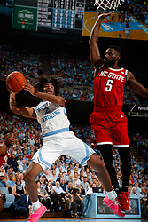 CHAPEL HILL, NC - FEBRUARY 05: Coby White #2 of the North Carolina Tar Heels shoots the ball around Eric Lockett #5 of the North Carolina State Wolfpack on February 05, 2019 at the Dean Smith Center in Chapel Hill, North Carolina. North Carolina won 113-96. North Carolina wore retro uniforms to honor the 50th anniversary of the 1967-69 team. (Photo by Peyton Williams/UNC/Getty Images) *** Local Caption *** Coby White;Eric Lockett