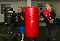 """Richard """"Flash"""" Laflamme and Barbara """"Bruiser"""" Lewis take a round with the punching bags during their """"Rock Steady Boxing"""" class at the Downtown Gym on Thursday evening.  (Karen Bobotas/for the Laconia Daily Sun)"""