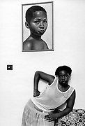Women beneath portrait of boy crying. Photo by Richard Saunders 1983