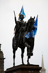 © Licensed to London News Pictures. 18/09/2014. Glasgow, UK. Scottish Saltire flags were left on a statue at George Square in Glasgow to whilst people going to polling stations to vote on the Scottish independence referendum on Thursday, 18 September 2014. Photo credit : Tolga Akmen/LNP