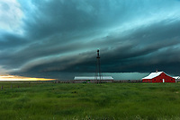A shelf cloud passes over a red barn near Denton, Montana.