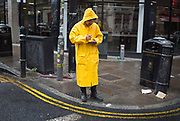 Man wearing a yellow waterproof coat gives out flyers on Brick Lane in the East End of London, UK.