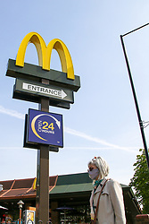 © Licensed to London News Pictures. 07/05/2020. London, UK. A woman wearing a face covering walks past McDonalds restaurant in north London. McDonalds restaurants have been closed since 23 March following coronavirus lockdown to slow the spread of the COVID-19 . The company has announced that 15 restaurants will open on 13 May. Photo credit: Dinendra Haria/LNP