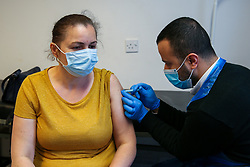 © Licensed to London News Pictures. 23/05/2021. London, UK. Pharmacist, Huseyin Akpinar administers the AstraZeneca vaccine to a woman at a vaccination centre in Tottenham, north London. A Public Health England study has revealed that both the Pfizer and AstraZeneca jabs are effective against the Indian Covid-19 variant, after both doses.  Photo credit: Dinendra Haria/LNP