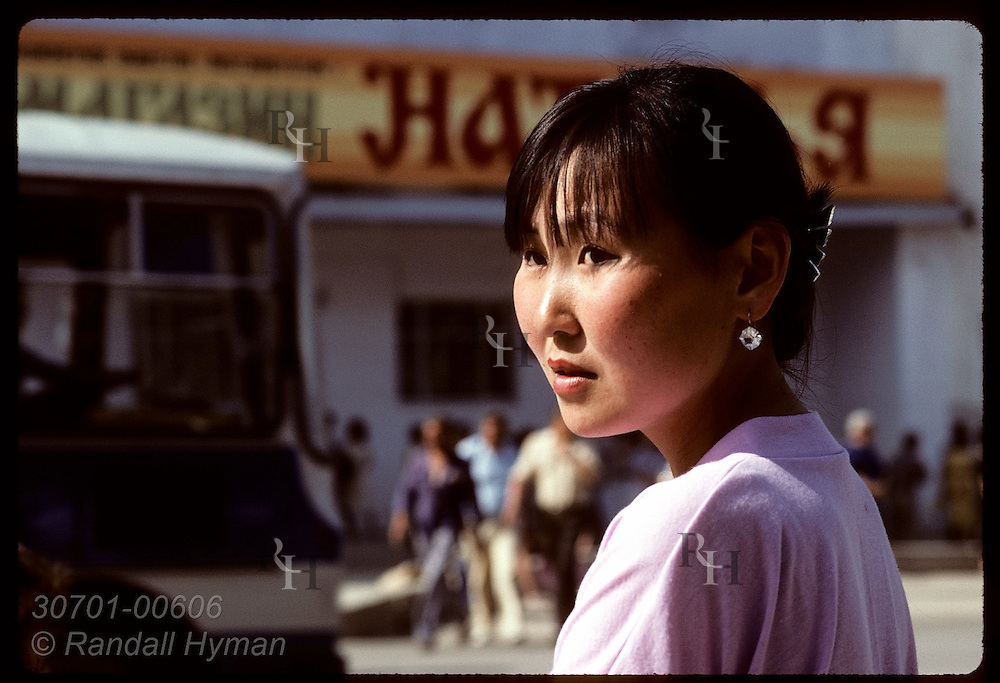 Young Sakha woman glances to side as she waits for bus on a June day on busy street in Yakutsk. Russia