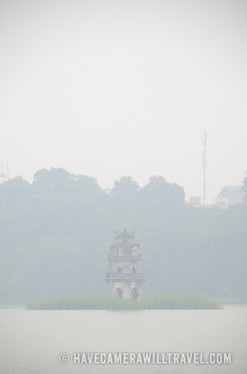 Turtle Tower (Thap Rua), on a small island in the middle of Hoan Kiem Lake in the heart of Hanoi is partially obscured by a thick morning fog. Copyspace at top of frame.