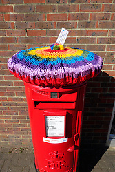 Rainbow thank you knitted cosy on top of Royal Mail post box during Coronavirus pandemic, Reading, UK February 2021