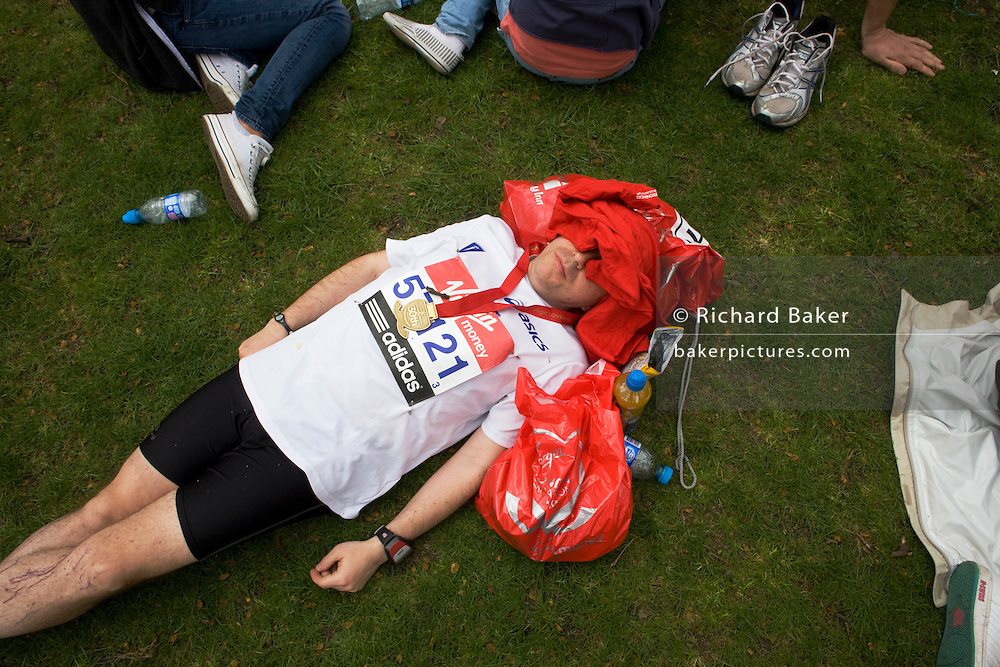 With face covered and medal around neck, a London Marathon runner collapsed on grass, before being met by family