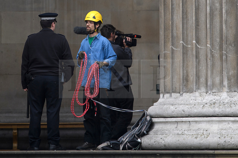 © Licensed to London News Pictures. 19/05/2016. London, UK. A climber who scaled the building being questioned by a police officer after climbing down. A Greenpeace protest by Greenpeace at the British museum which has closed the museum. Greenpeace climbers have scaled pillars at the museum, erecting banners protesting against BP sponsorship of Sunken Cities: Egypts - Lost Worlds exhibition at the museum. Photo credit: Ben Cawthra/LNP