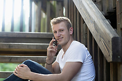 Young man talking on mobile phone on staircases, Freiburg im Breisgau, Baden-Wuerttemberg, Germany
