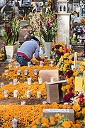 A Purepecha indigenous man decorates the grave of a relative for the Day of the Dead festival October 31, 2017 in Tzintzuntzan, Michoacan, Mexico.