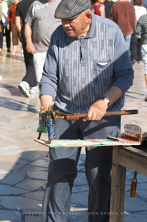 A street entertainer, old man showing to children two carved wooden dancing dolls Sanary Var Cote d'Azur France