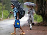 A schoolboy holding umbrella crosses road during the monsoon rains, Mangalore, Karnataka, India