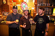 Three bartenders playing around with beer behind the bar at the Deschutes Brewery in downtown Bend, Oregon