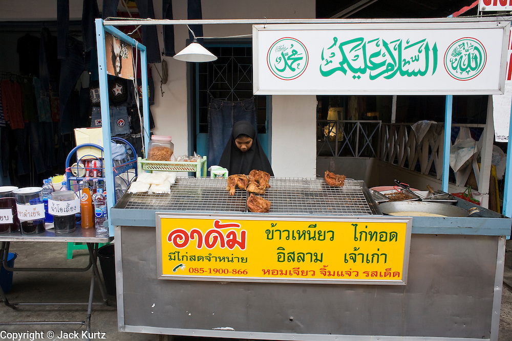 20 FEBRUARY 2008 -- KANCHANABURI, THAILAND: A Moslem woman at her food stand in Kanchanaburi, Thailand. Thailand's Moslem population is growing rapidly. Thai Moslems in the south of the country are waging a bloody insurrection against the Buddhist government in Bangkok.  Photo by Jack Kurtz