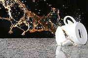A coffee cup smashes on the ground with a high-speed flash capturing the action at 1/15,000th of a second.