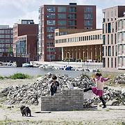Nederland Amsterdam 15-09-2010 20100915..Nieuwbouw wijk IJburg, woningen in het hogere segment. Kinderen bouwen van bakstenen een eigen huisje op braakliggend terrein dat nog bebeouwd zal gaan worden.  IJburg is een woonwijk in aanbouw in het oosten van de gemeente Amsterdam, in de Nederlandse provincie Noord-Holland. Kenmerkend aan de in het IJmeer gelegen wijk is dat deze op kunstmatige eilanden is gebouwd. IJburg maakt onderdeel uit van het stadsdeel Oost. Holland, The Netherlands, dutch, Pays Bas, Europe , Yburg, het Ij, Het Y, , gebiedsontwikkeling, waterwijk, waterwijken, waterwoning, waterwoningen, wijk, wijken, wonen aan het water, woning, woningaanbod, woningbouw, woningen, woningmarkt, woningvoorraad, woonbuurt, woonbuurten, woonlast, woonlasten, woonwijk, woonwijken, straatbeeld, straatgezicht, toekomstige plannen, uitbreidingsgebieden, vastgoed, vernieuwing, vernieuwing stedelijk, verstedelijking, vessel, vinex, vinex-locaties, vinex-wijken, vinexbuurt, vinexlocatie, vinexlokatie, vinexwijk, volkshuisvesting, voorgevel, woning, woningaanbod, woningbehoefte, woningblok, woningblokken, woningbouw, woningen, woningkopers, woningmarkt, woningvoorraad, woonblok, woonblokken, woongebied, woonlast, woonlasten, zichzelf vermaken..Foto: David Rozing