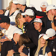 Ryder Cup 2016. Day Three. The United States team players and their spouses and partners kiss as partnerless Rickie Fowler stands alone during Ryder Cup celebrateions after the United States victory in the Ryder Cup tournament at Hazeltine National Golf Club on October 02, 2016 in Chaska, Minnesota.  (Photo by Tim Clayton/Corbis via Getty Images)