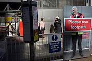 Footpath disruption sign using illustration of TFL workman, with background of Victoria bus passengers.