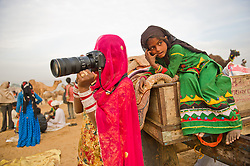 Subita Devi, uses a professional camera while her sister Lila watch tourists at the world's largest annual cattle fair in the desert town of Pushkar, in the Indian state of Rajasthan. Every year thousands of camel herders from the semi-nomadic Rabari tribe, who make a living rearing animals, travel for two to three weeks across 500 kilometers to set up camp in the desert dunes near Pushkar to sell their livestock. The herders sell more than 20,000 camels, horses and other animals at the annual cattle fair.